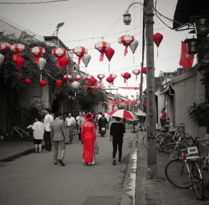 Vietnamese woman in traditional dress walking down one of the main streets